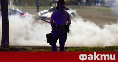 Полицай притиска с коляното си гърлото на повален на земята